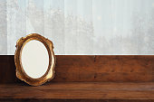 Golden old blank frame on wooden window sill