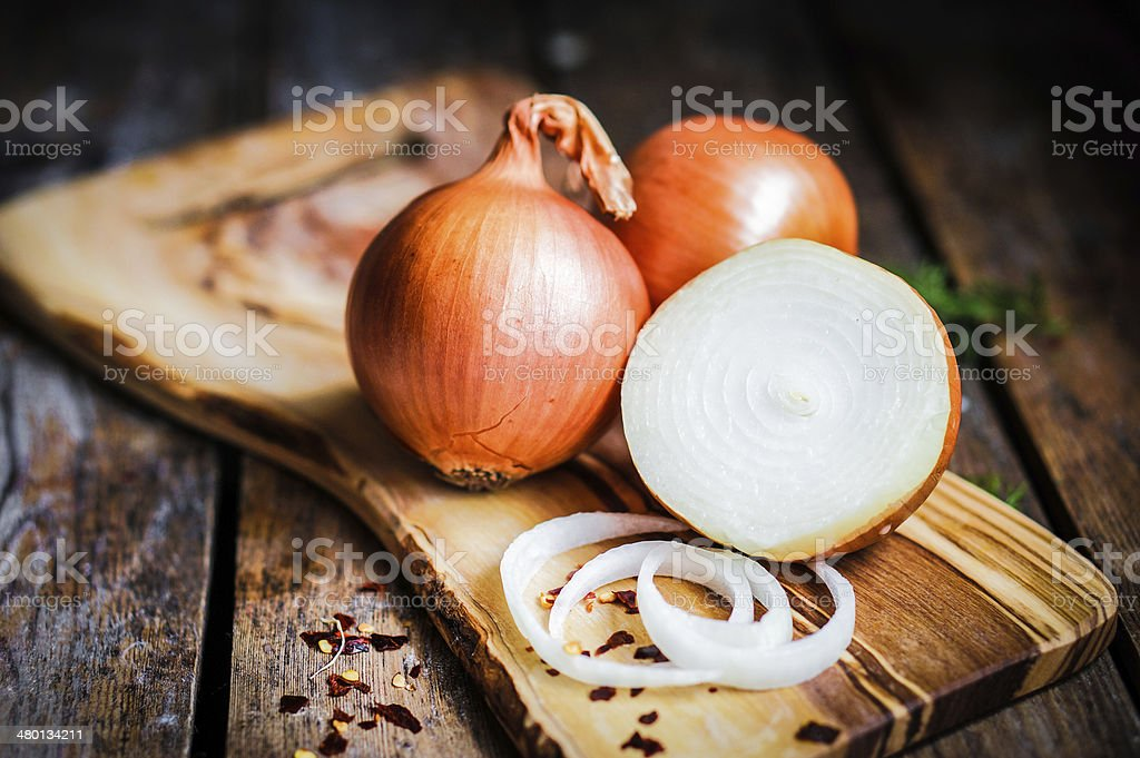 Golden onions on rustic wooden background stock photo