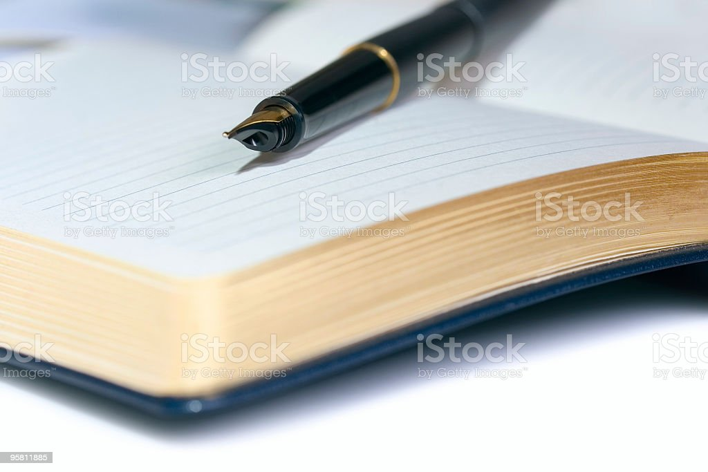 golden pen and notebook stock photo