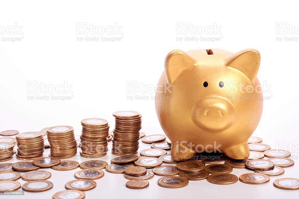 Golden piggy bank and coins of the Brazilian money stock photo