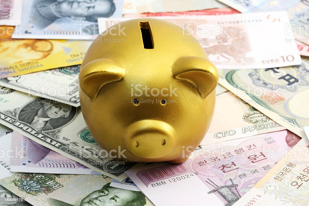 Golden piggy bank and currency royalty-free stock photo