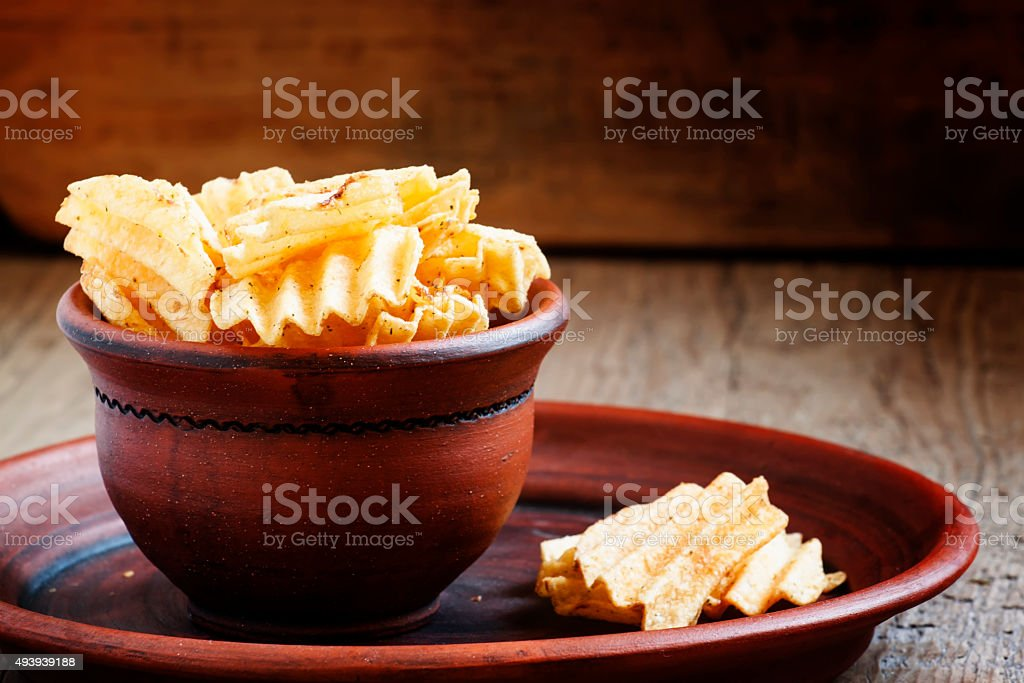 Golden potato chips in clay bowl on the old table stock photo