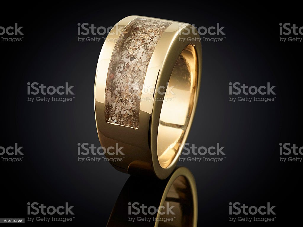 Golden ring with ashes isolated on black stock photo