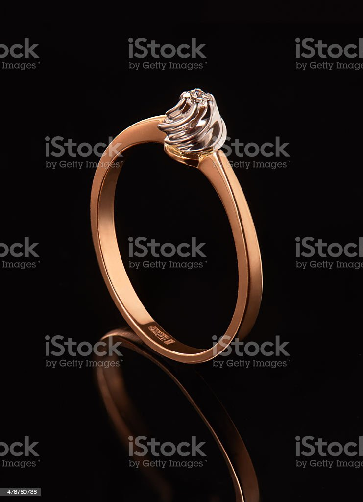 Golden ring with diamond, isolated on black background stock photo