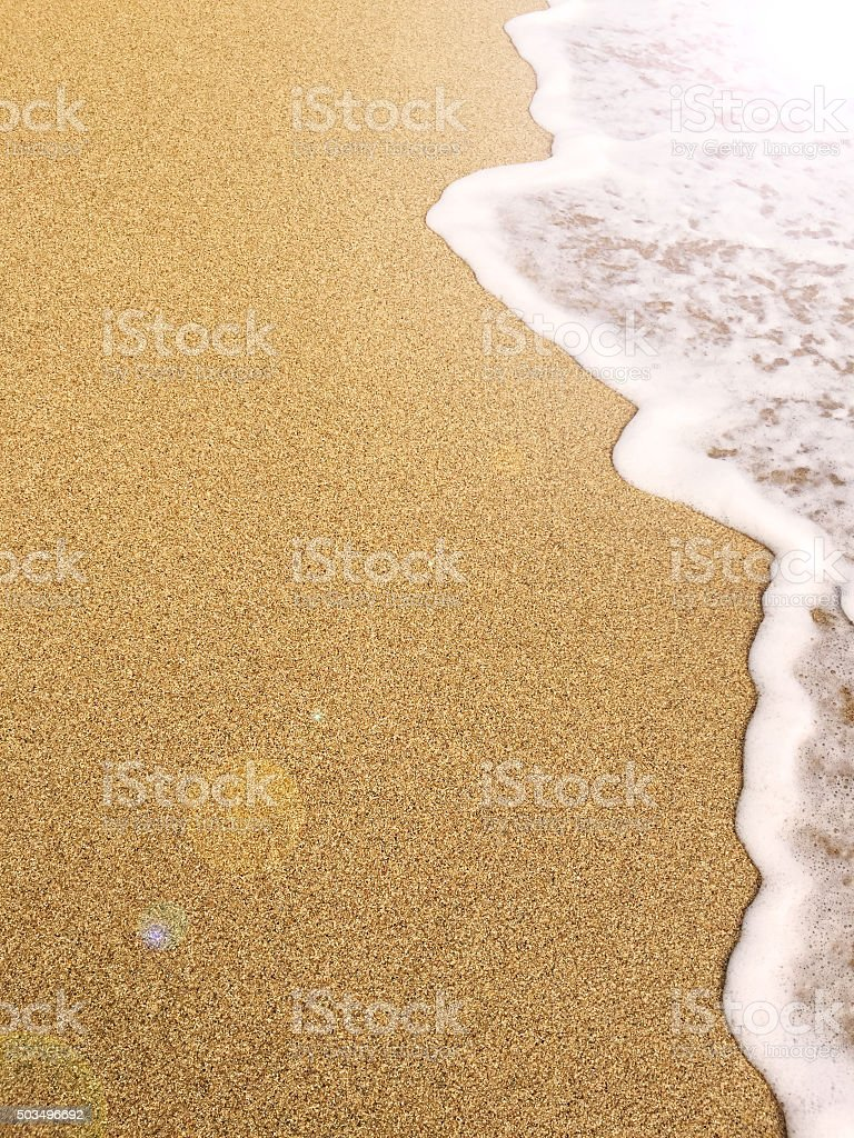 Golden sand beach and frothy sea foam waves stock photo