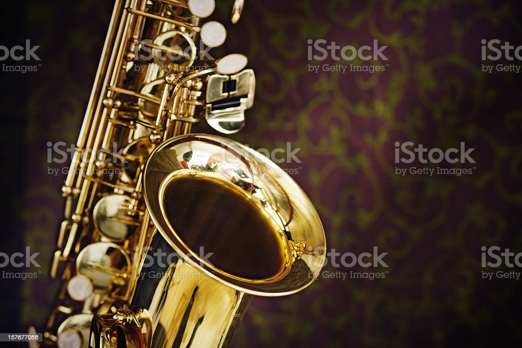 Golden saxophone gleams against a background of richly figured silk stock photo