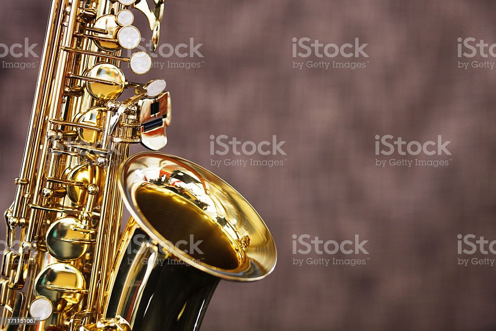 Golden saxophone shines against a dark out-of-focus background royalty-free stock photo