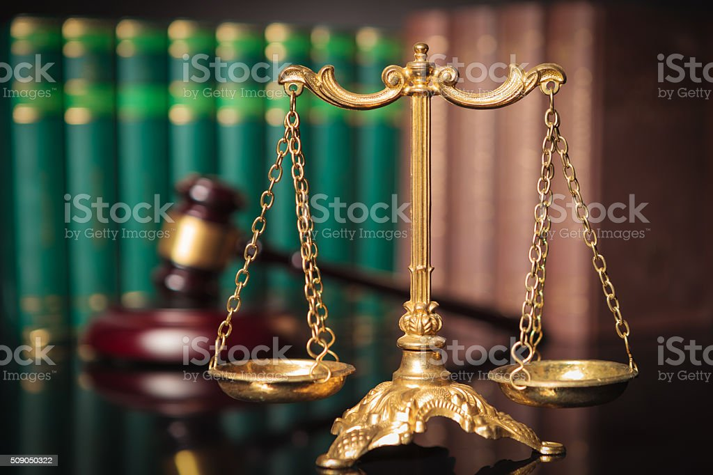 golden scale in front of judge's gavel and law books stock photo