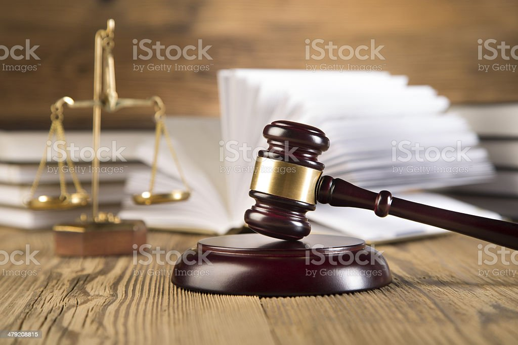 Golden scales of justice, gavel and books wood brown background stock photo
