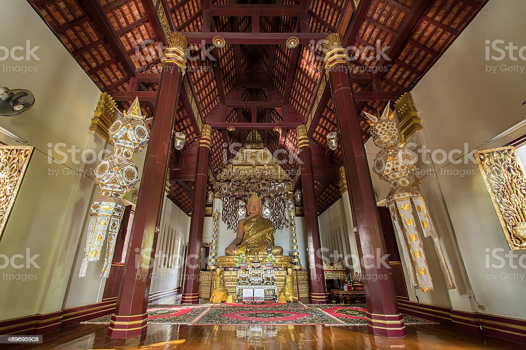 Golden seated presiding Buddha in Phra That Chom Kitti temple, stock photo
