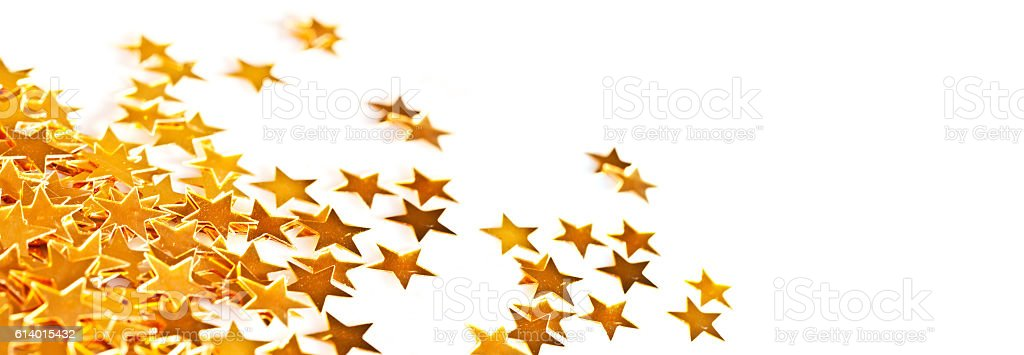 Golden shiny little stars table ornaments on white, holiday header stock photo