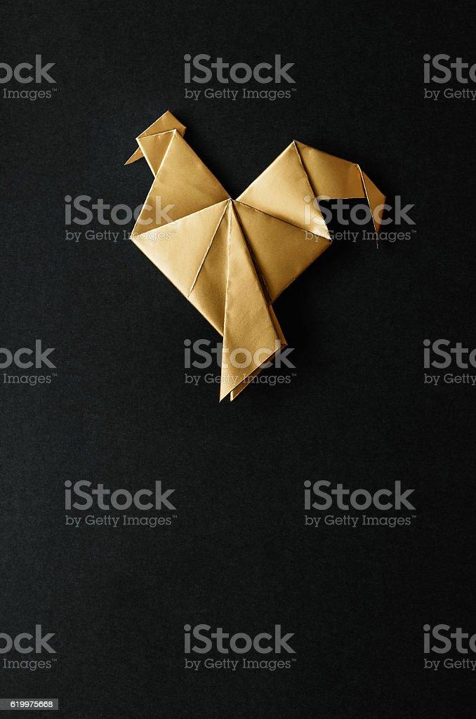 Golden shiny paper folded rooster handmade origam stock photo