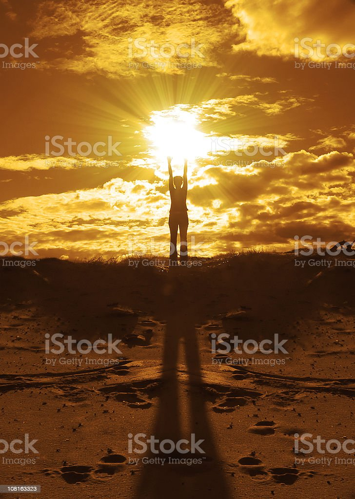 Golden Silhouette of Woman Doing Yoga Pose at Sunset royalty-free stock photo