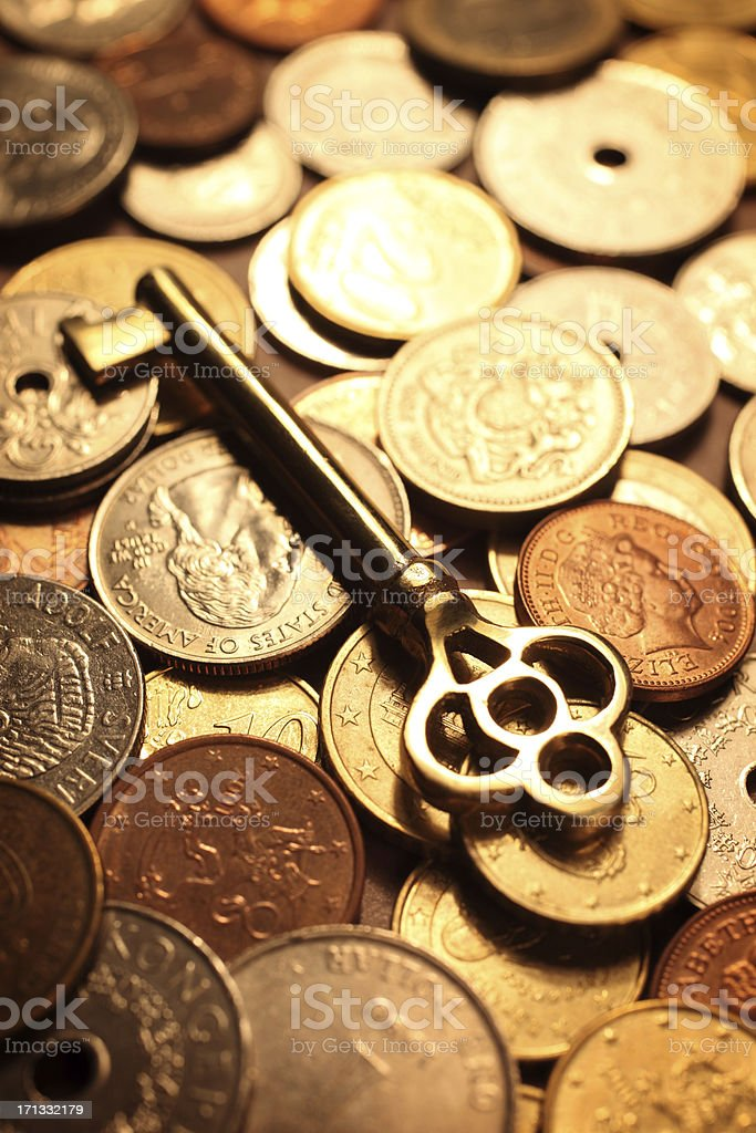 Golden Skeleton Key on a Pile of Coins royalty-free stock photo