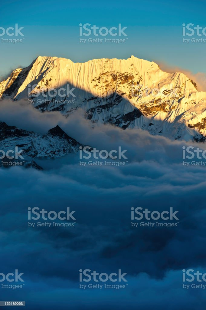 Golden snow sunlight summits above the clouds Himalayas Nepal stock photo