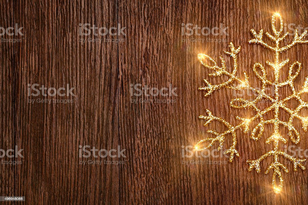 Golden snowflake on grunge wooden texture background stock photo