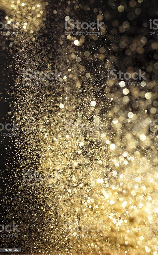 Golden splashing raindrops in the light stock photo