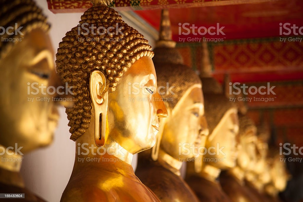 Golden statues all in line in Bangkok royalty-free stock photo