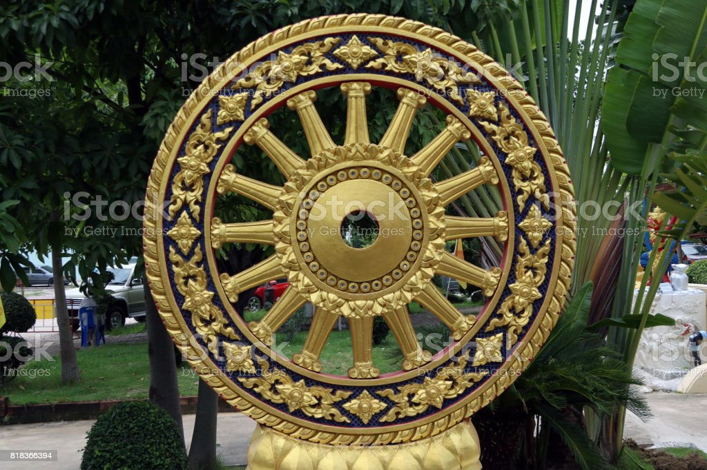 Golden stucco of the Wheel of the dharma and decorate by little blue glass. stock photo