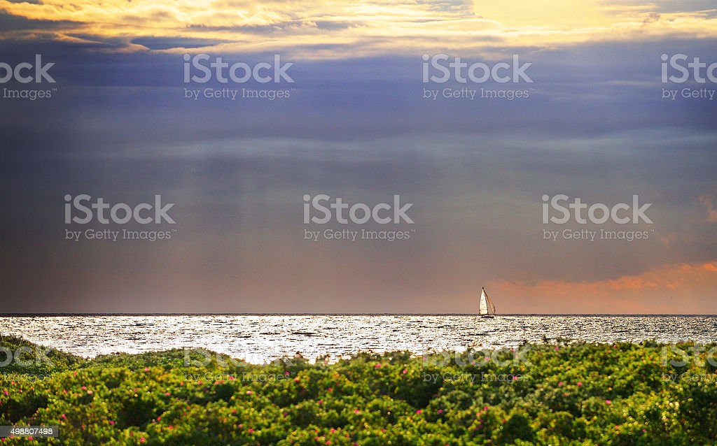 Golden sunbeam flowing over sailing ship and calm sea stock photo
