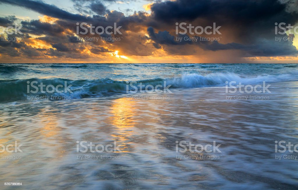 Golden sunbeams penetrating the storm clouds over the Miami coast stock photo