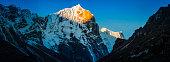 Golden sunlight illuminating snowy peak Parchemuche overlooking Himalayan monastery Nepal