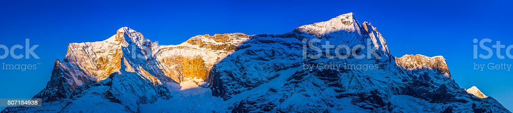 Golden sunlight of daybreak illuminating snowy mountain peaks panorama Himalayas stock photo