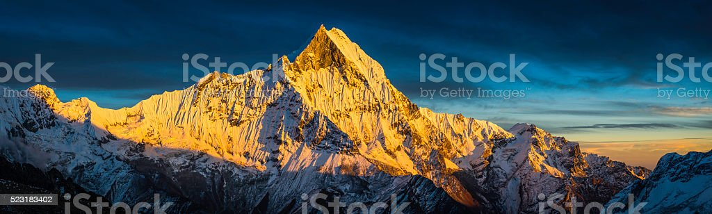 Golden sunlight on sacred mountain peak panorama Machapuchare Himalayas Nepal stock photo