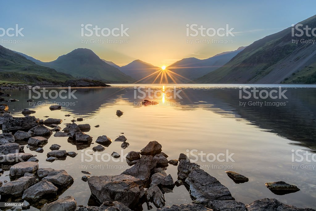 Golden sunrise at Wastwater lake with rocks and mountains. stock photo