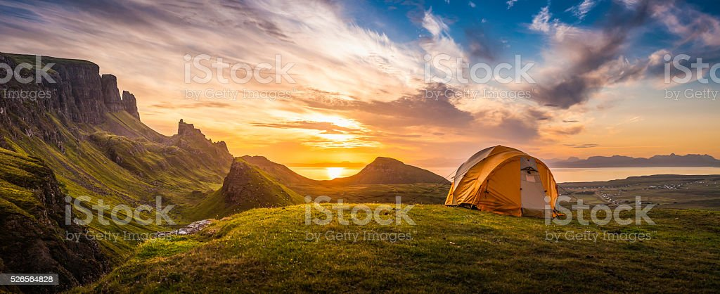 Golden sunrise illuminating tent camping dramatic mountain landscape panorama Scotland stock photo