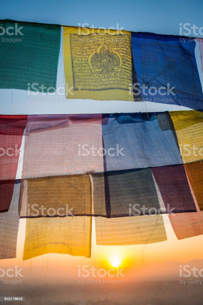 Golden sunrise illuminating vibrant Buddhist prayer flags above Kathmandu Nepal stock photo
