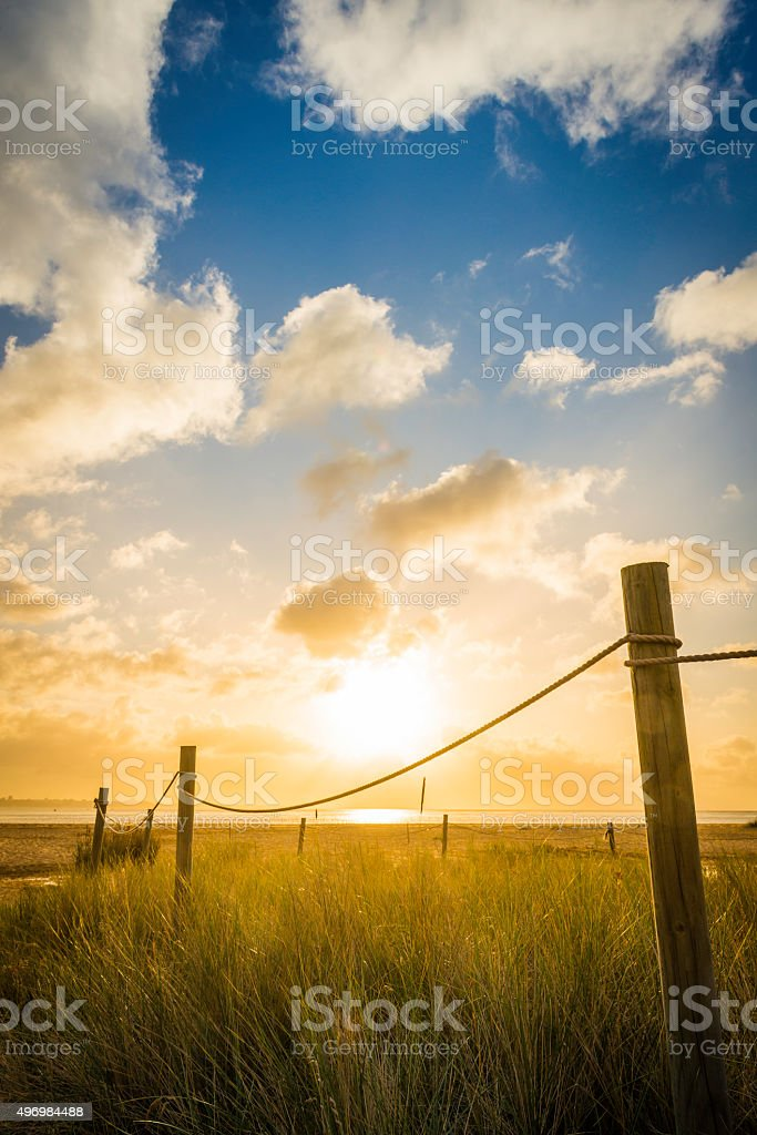 Golden sunrise over sand dunes rope walkway to tranquil ocean stock photo