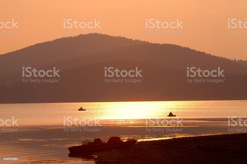 golden sunset in mountain lake stock photo