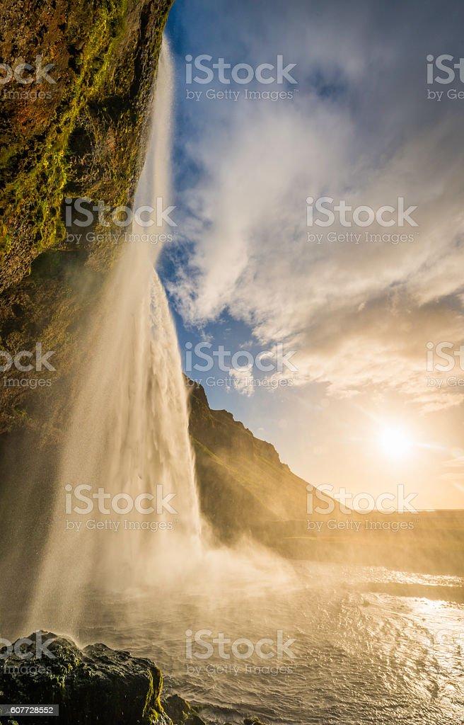 Golden sunset light illuminating mountain waterfall cascading over cliff Iceland stock photo