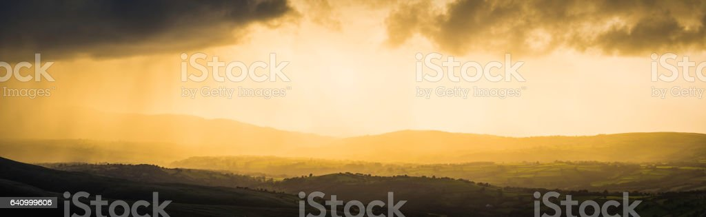 Golden sunset light silhouetting hills mountains through clearing storm panorama stock photo