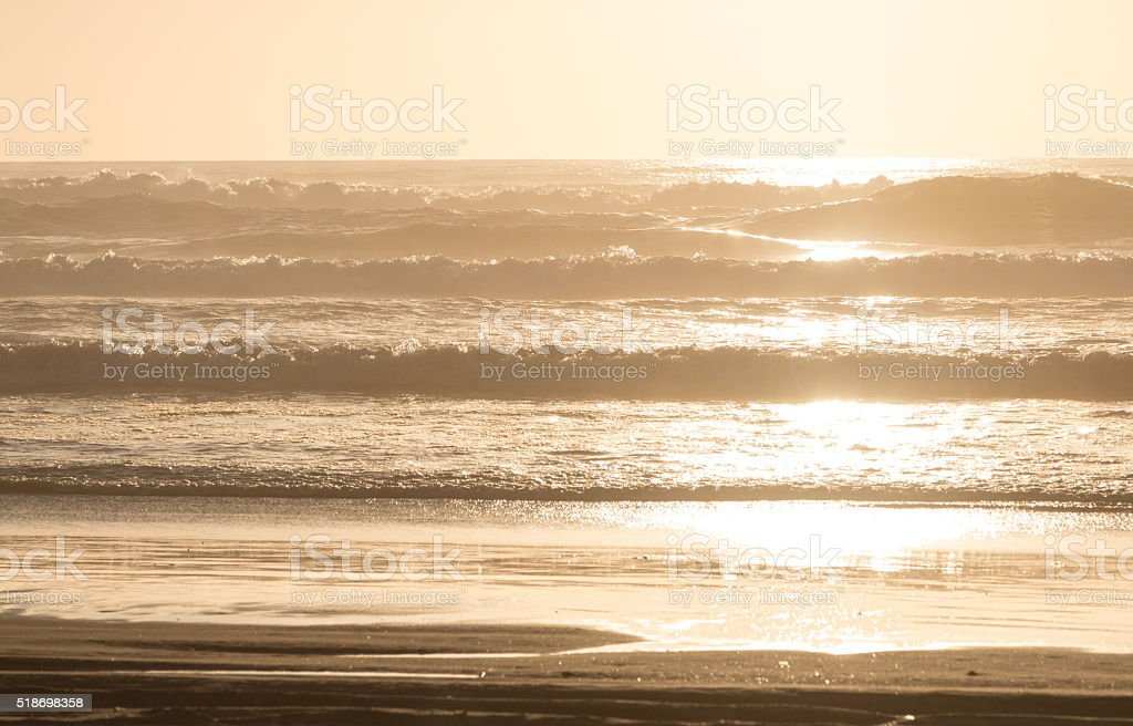 Golden sunset on beach with waves stock photo