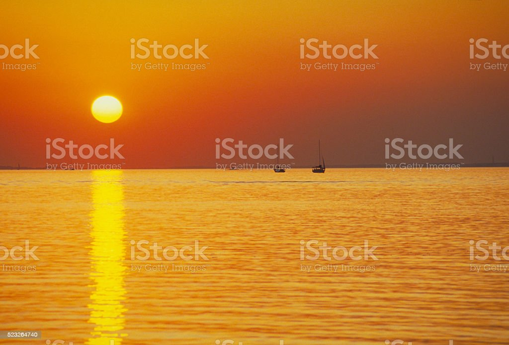 Golden Sunset Reflected on Calm Bay stock photo