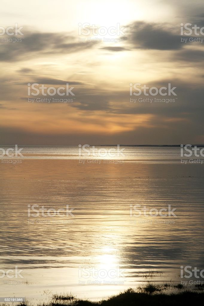 Golden sunset with reflection in calm sea stock photo