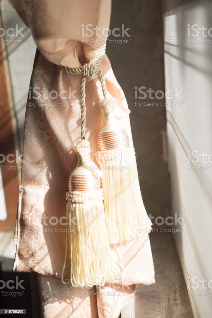Golden tassel holding back curtains with sunlight stock photo