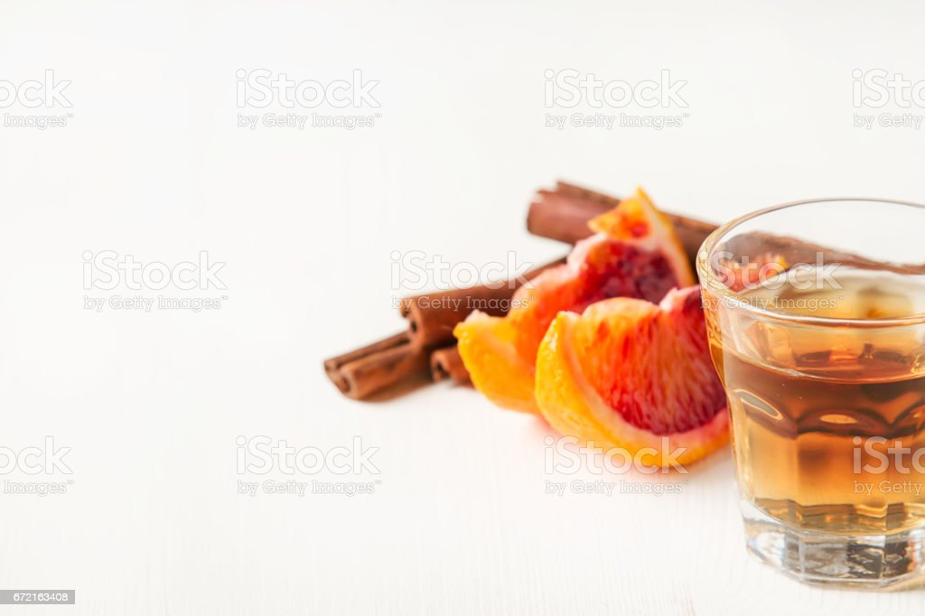 Golden tequila with red orange and cinnamon. Light white background. Selective focus stock photo