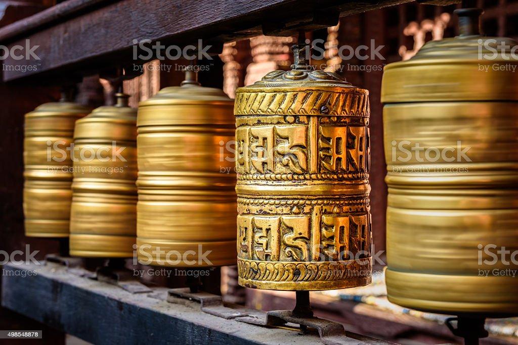 Golden tibetan prayer wheels in a Buddhist temple in Nepal stock photo