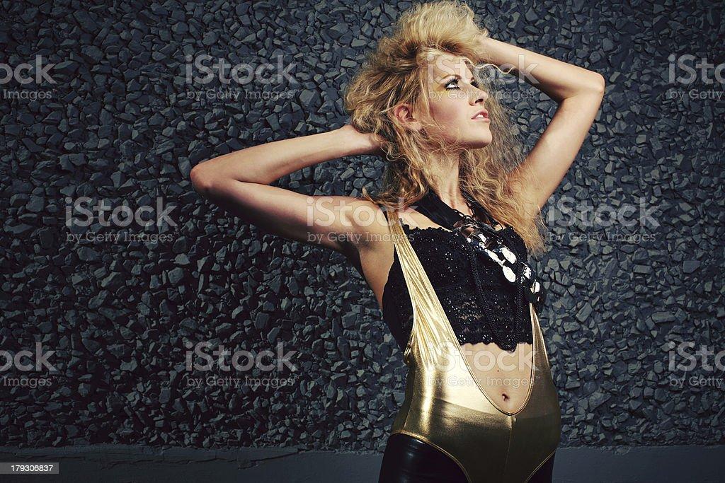 Golden Unitard Blonde Girl on Black Holding Big Hair royalty-free stock photo