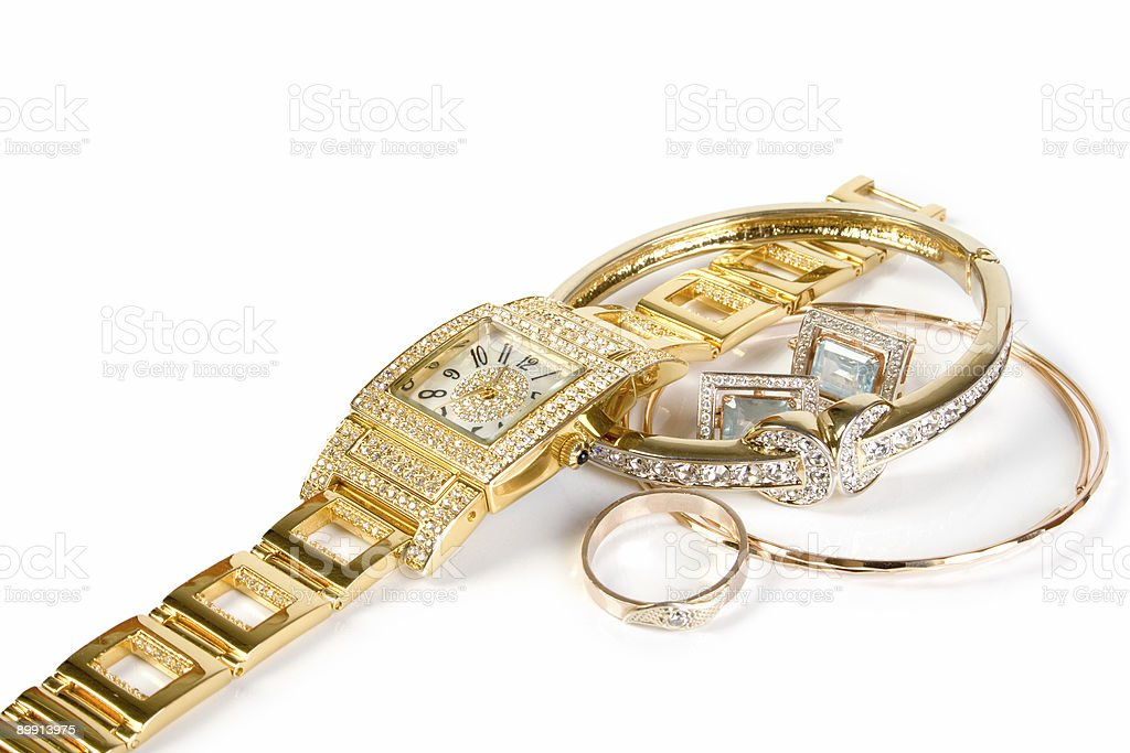 Golden watch and jewellery piled on a white background royalty-free stock photo
