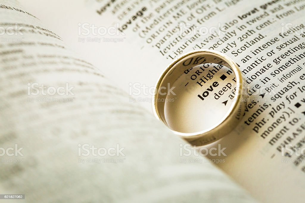 Golden wedding ring placed over word 'love' in dictionary stock photo
