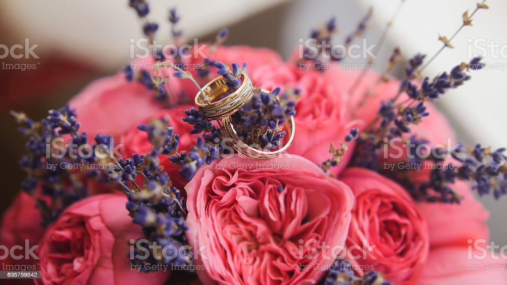 Golden wedding rings in center of bride's bouquet stock photo