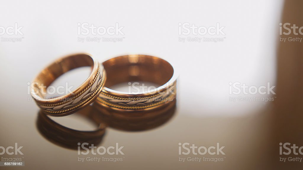 Golden wedding rings on mirror glasses table - one lies stock photo
