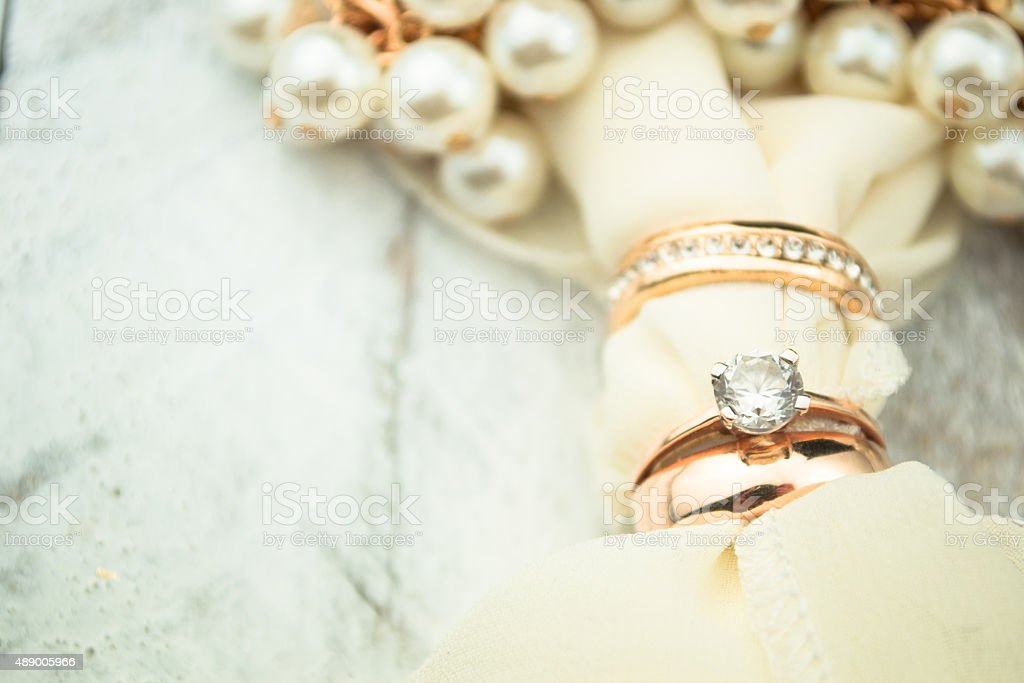 Golden wedding rings on white wood background stock photo
