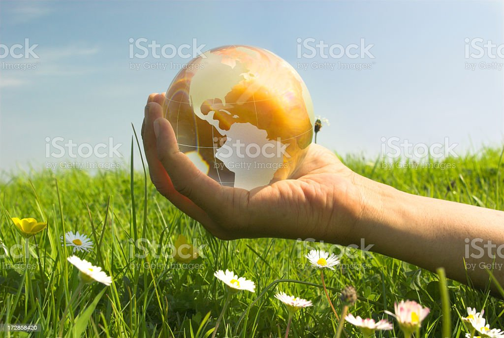 A golden world globe held by a hand in a field of grass stock photo