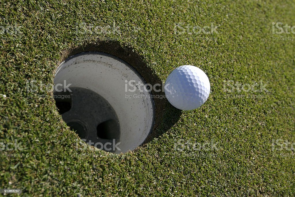 golf ball about to roll in hole stock photo