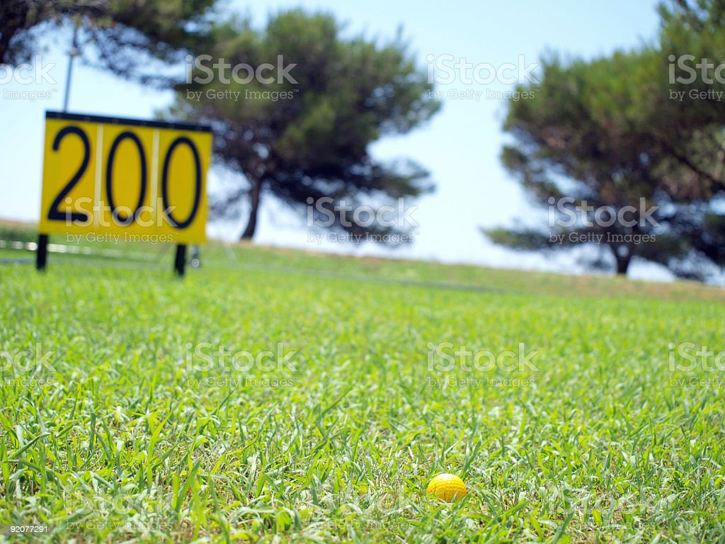 Golf ball and 200 meter/yard sign on driving range stock photo